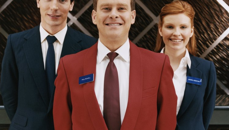 Portrait of Three Hotel Reception Staff Standing With Their Hands Behind Their Backs