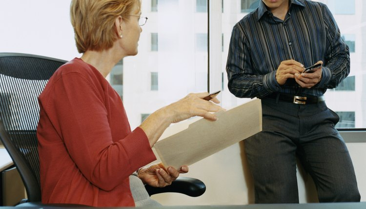 Mature Businesswoman Sits at a Desk Giving Orders From a Document to a Work Colleague