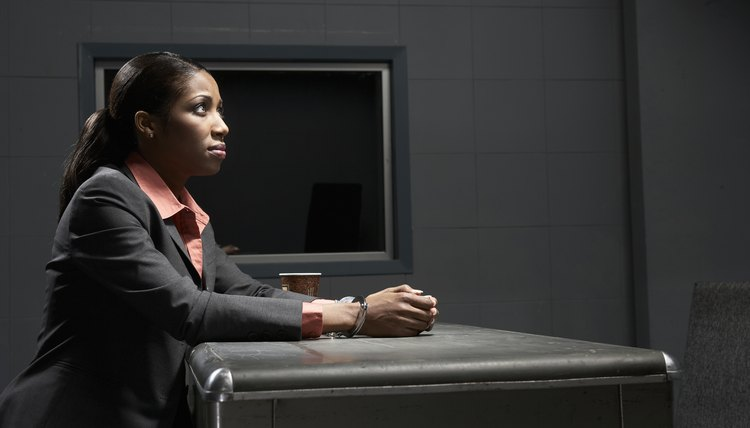 Young handcuffed woman sitting at desk in interrogation room, side view