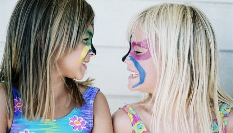 Two girls with their faces painted.