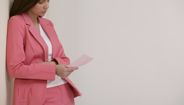 Businesswoman looking at pink slip