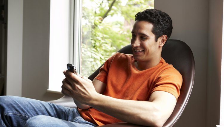 Latino man text-messaging at home by window