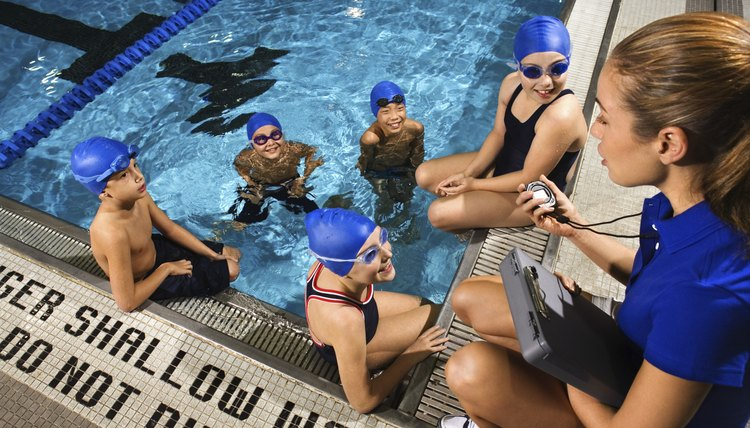 Swim instructor speaking with young swimmers.