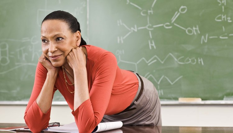 Teacher leaning on desk by chalkboard