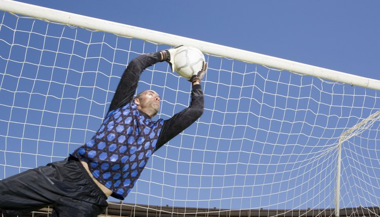 If a Soccer Goalie Has His Hand on the Ball Can a Player Kick It?