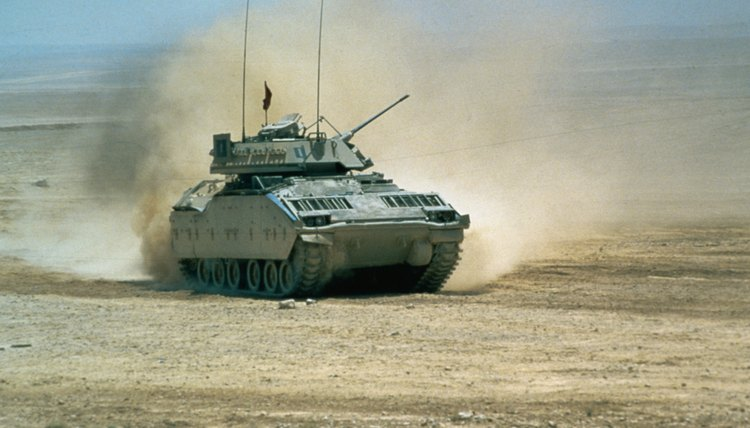 Military tank going through desert