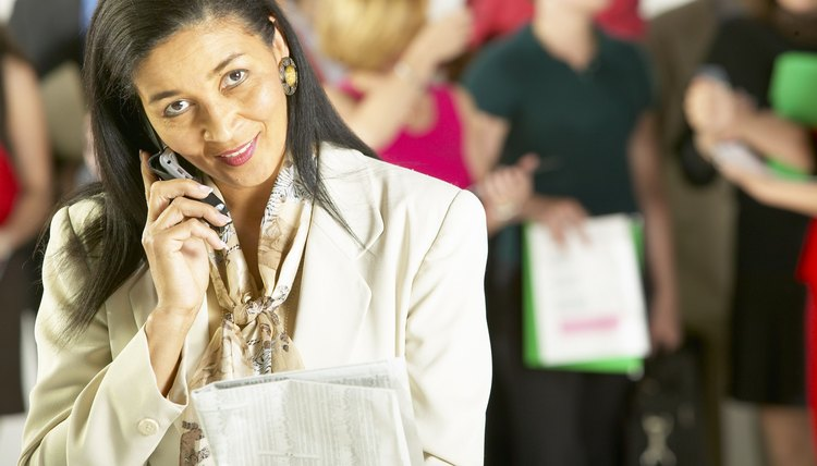 businesswoman on cell phone with job applicants