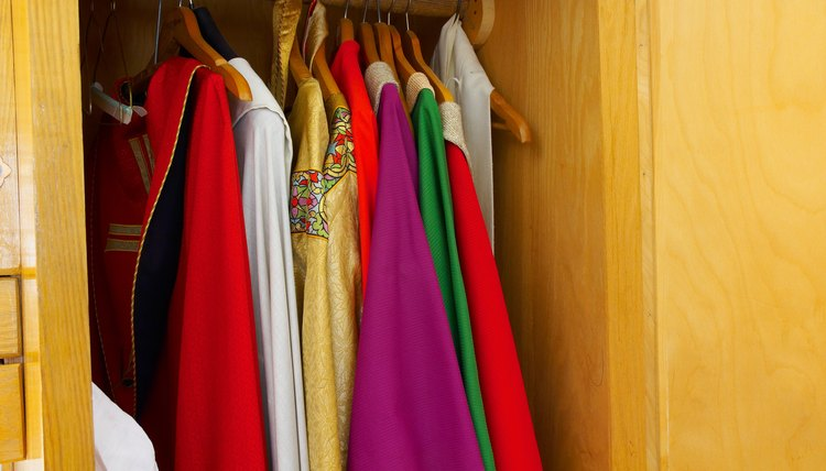 Various clergy robes hang in a closet.