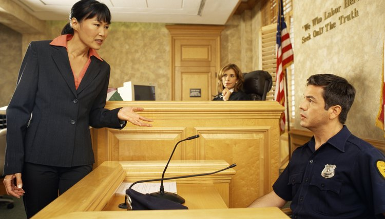 Side profile of a witness and a lawyer on the witness stand, with the judge listening