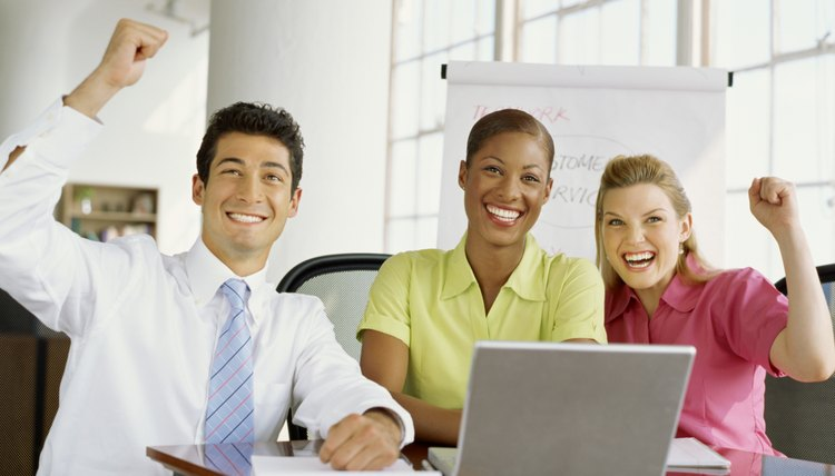 two businesswomen and a businessman smiling in a meeting