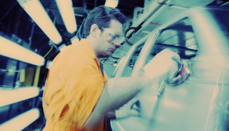 Male worker on assembly line in car manufacturing plant