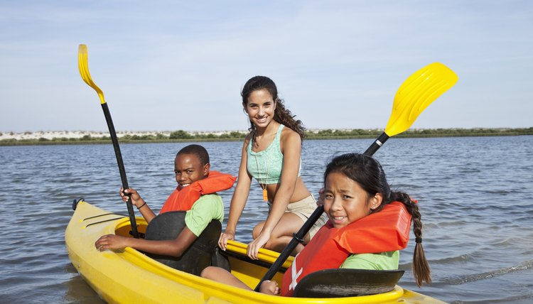 Camp counselor with children in kayak