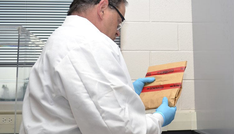 A forensics scientist holds an envelope containing evidence from a crime scene.