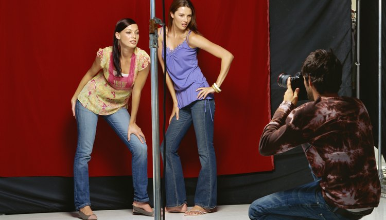 Rear view of a photographer photographing two young women