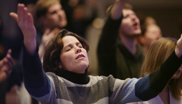 Woman singing worship music wit her arms lifted.
