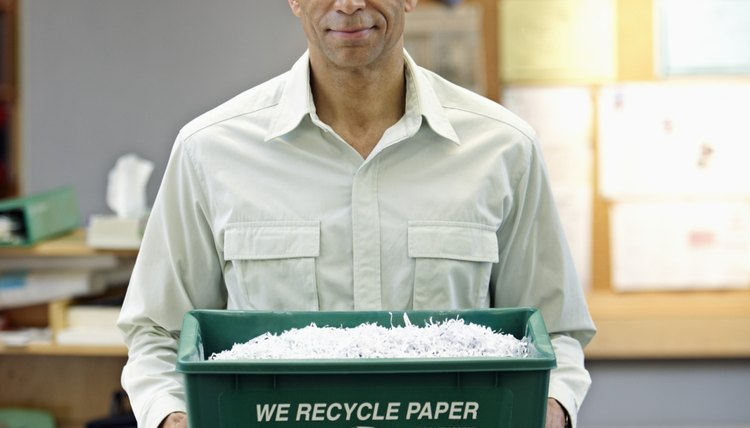 An employee holds a recycling bin for paper in an office.
