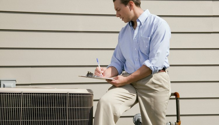 Man with clipboard near air conditioning unit