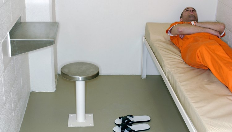 Inmate lying on bed in prison