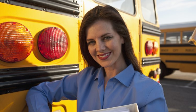 teacher leaning on a school bus