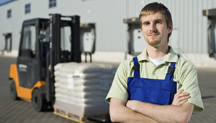 Smiling worker near loading dock with forklift
