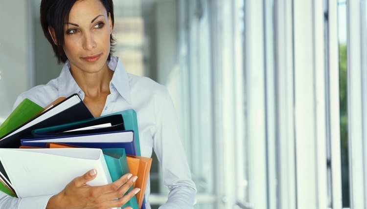businesswoman holding a stack of files in an office