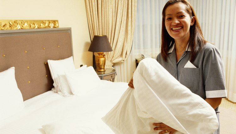 Uniformed maid holding pillow in hotel room, smiling
