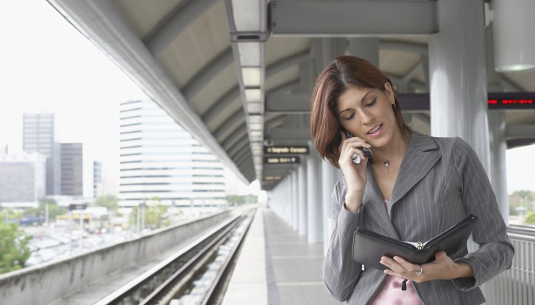 Young woman talking on a mobile phone at a train station
