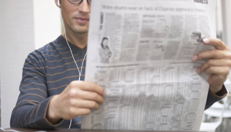 Man sitting at cafe table reading newspaper, wearing earphones