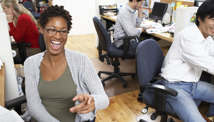 Group of office workers at desks, woman laughing