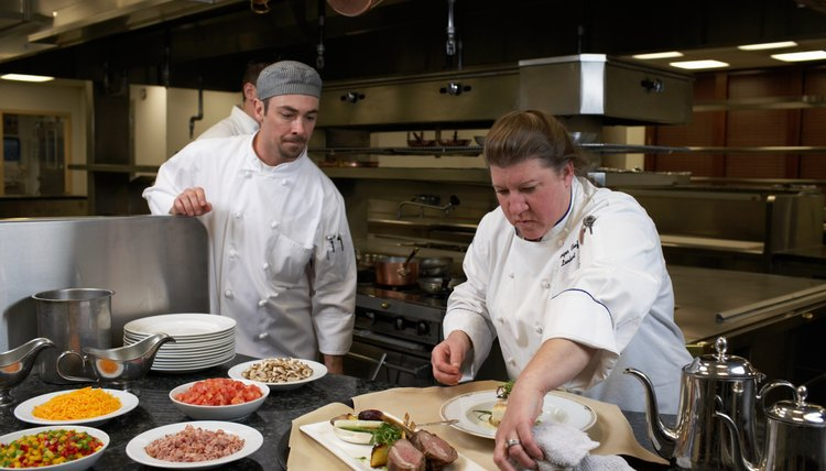 Three Chefs Working In Commercial Kitchen