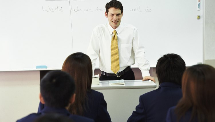 English teacher standing at front of classroom.