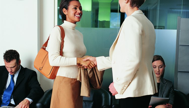 Businesswoman Greeting a Young, Female Interviewee in an Office