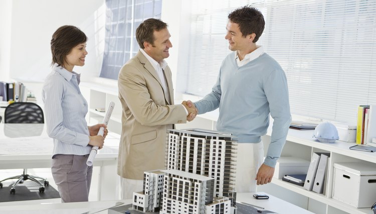 Architects shaking hands next to scale model