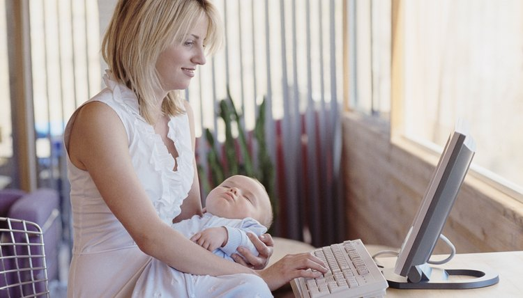 Mother using computer and holding baby