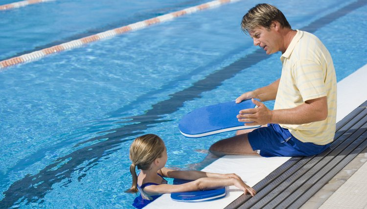Man giving swimming aid to girl
