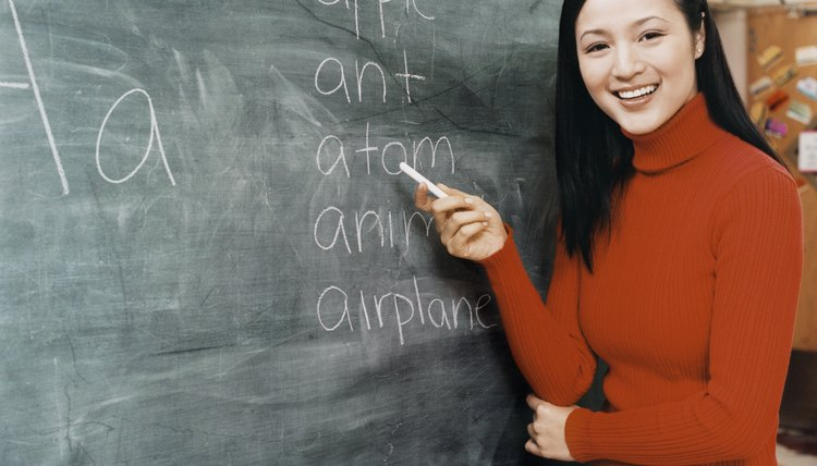 Thirtysomething Female Teacher Pointing at Words on a Blackboard With Chalk