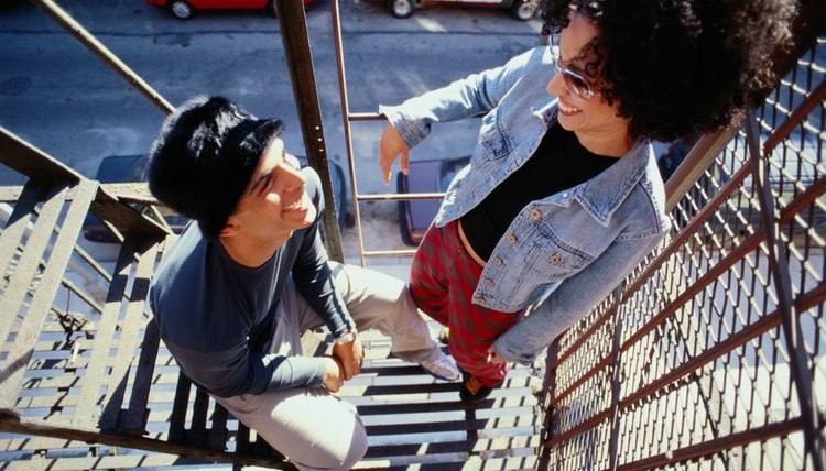 Two young adults hanging out on a fire escape outside of a city loft.