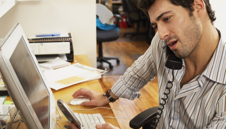 Male office worker using telephone, balancing handset against shoulder