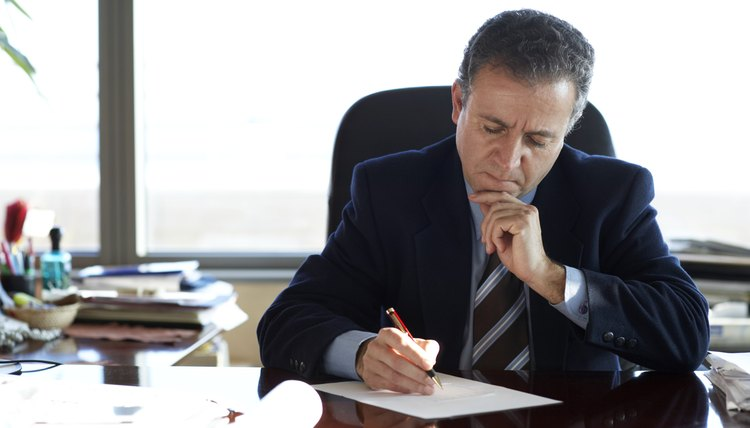 Mature businessman writing at desk