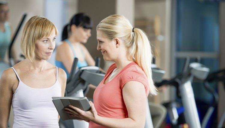 Young female with personal trainer at gym.