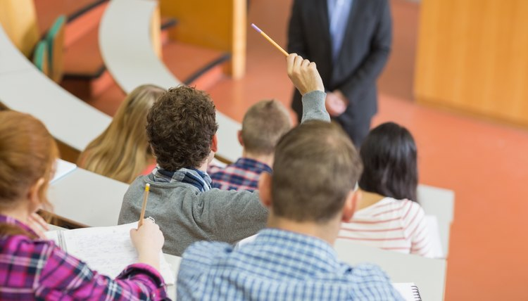 Student raising hand in lecture hall.