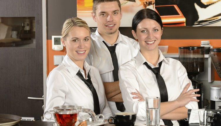 Three uniformed server posing in cafe