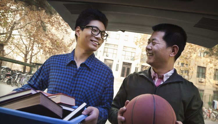Father helping his son move into college with basketball in hand.