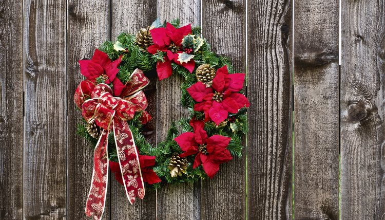 Poinsettia and garland Christmas wreath on a wood surface.