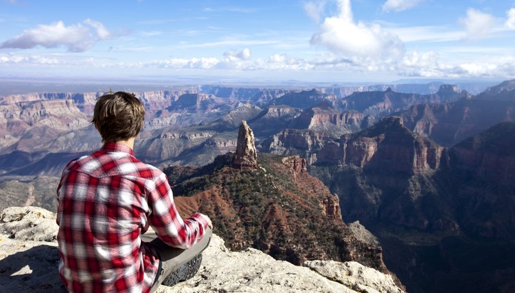 A young man sitting on a rock to take in the view.