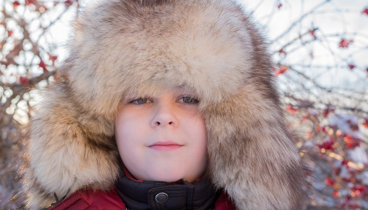 A portrait of a boy in a thick fur hat.