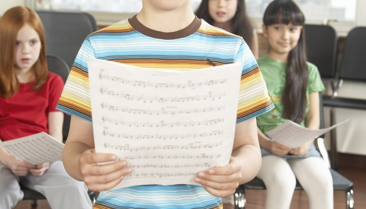 Young student singing while holding sheet music.