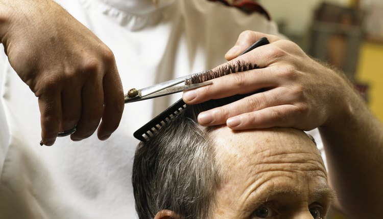 Barber cutting senior man's hair, close-up of hands