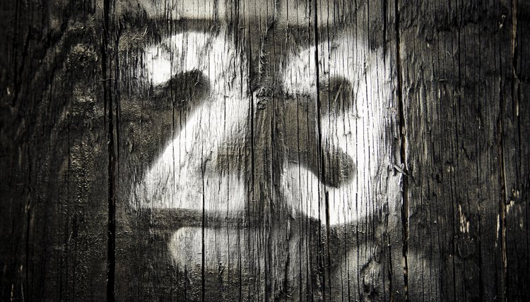 The number 23 spray painted on a wooden fence.
