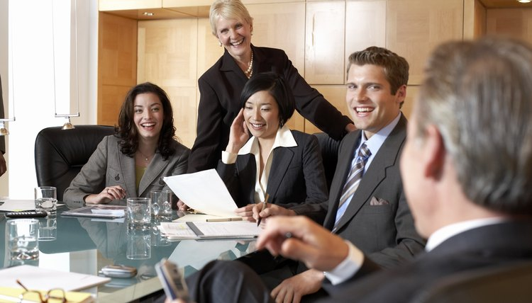Business people at conference table in meeting, smiling, close-up